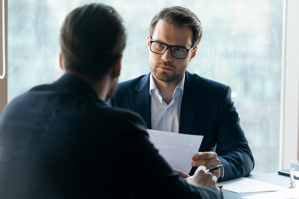 HR manager wearing glasses looking at job applicant